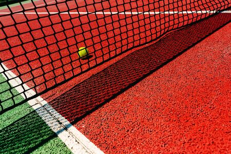 A tennis ball on the textured floor of a red court near the net after losing a match point. 写真素材