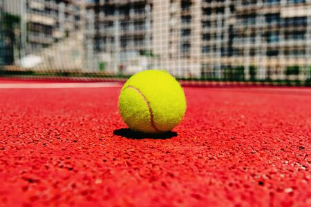 Yellow tennis ball on the red cement court to the sun, summer sports. 写真素材