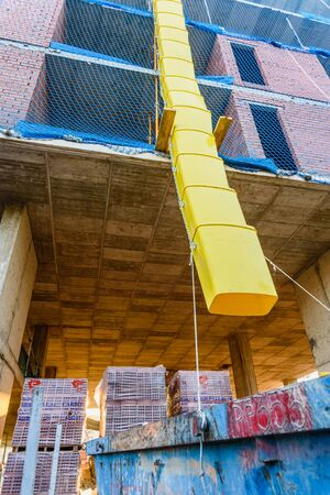 Valencia, Spain - July 3, 2019: Pipes to throw  debris into a construction site. 에디토리얼