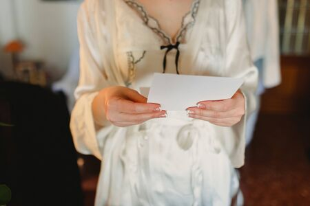 A woman in a white coat holds a letter and reads it.