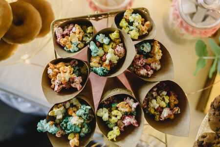 Pop corn in a candy bar beautifully decorated with sweets in a vintage event. Imagens