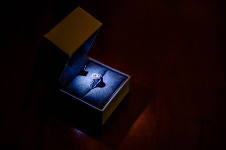 Ring with diamonds in its box, focally lit on a black isolated background.