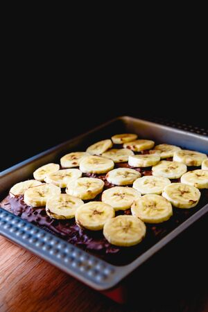 Sliced banana on a cake on a tray before baking it.