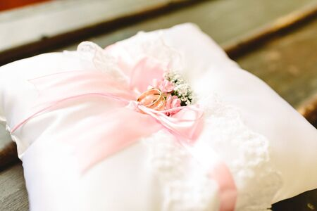 Wedding rings on a white cushion.