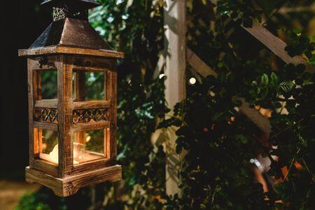 Wooden lantern lighting up the night in a garden. Imagens