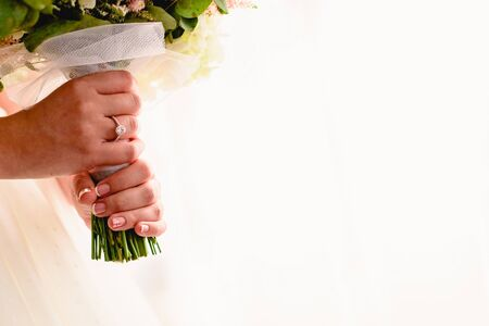 A womans hand with wedding ring while holding her bouquet, plenty of white copy space. 版權商用圖片