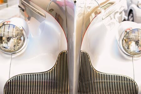 Headlights and radiator on the front of a vintage white sports car.