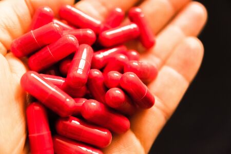 Mans hand holding a handful of medicine pills, to treat addictive diseases Imagens