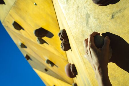 Climbers hands attached to the supports of an outdoor climbing wall. 版權商用圖片