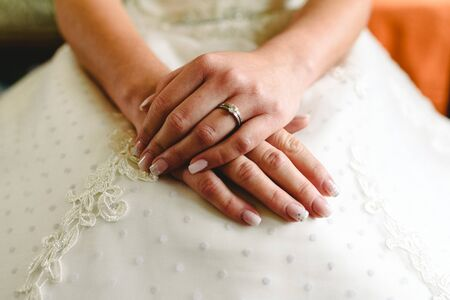 Wedding ring in the hands of a woman with her wedding dress. Stock Photo