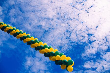 Row of colorful balloons crossing the blue sky with clouds, background with negative space for copy