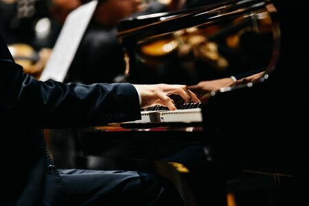 Pianist playing a piece on a grand piano at a concert, seen from the side. Stock Photo
