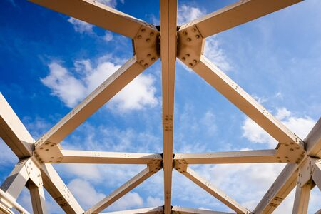 Metal structure of beams joined by screws, against the background sky. 版權商用圖片