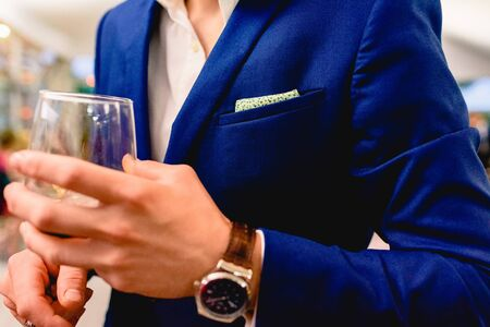 An elegant businessman holds a glass of wine during a business meeting. Stockfoto