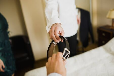 A man wears his wedding suit, while someone passes his belt with his hand.
