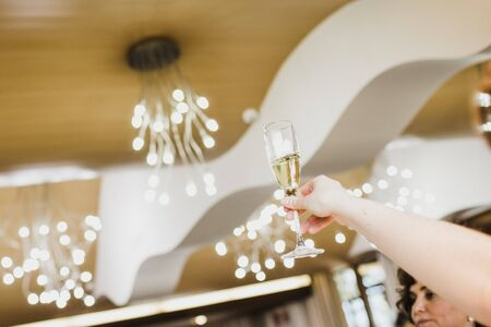 Woman raises a glass to toast during a wedding