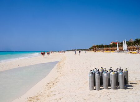 Playa del Carmen, Mexico - March 23, 2010: Several scuba diving tanks stacked on the beach to be used by a group of tourists who are going to dive in the Caribbean waters.