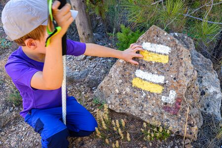 Child hiker next to a stone with markings and direction signs of the path.