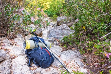 Backpack equipped for free camping in the mountains, on some rocks.