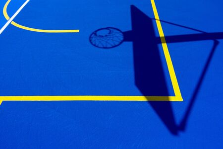 Shadow of a basketball basket on the floor of the court, painted blue and background with lines.