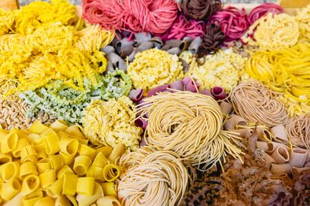 Many types of uncooked Italian pasta of various colors and shapes