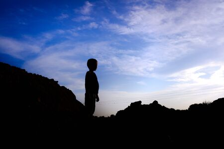 Silhouette of a child in backlight on a mountain. 写真素材