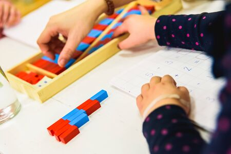 Little girl using painted wooden rods to learn to add in a school.