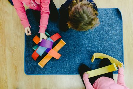 Group of girls playing in class with colorful wooden bows to build shapes.