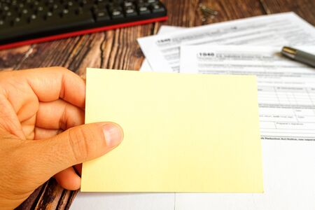 Yellow blank reminder card, held by a citizen on the day of tax payment of form 1040.