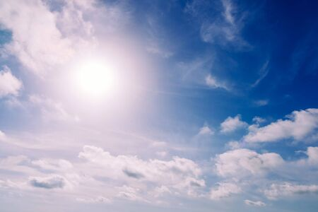 Glowing sun in a blue summer sky with nice white clouds. Stock fotó