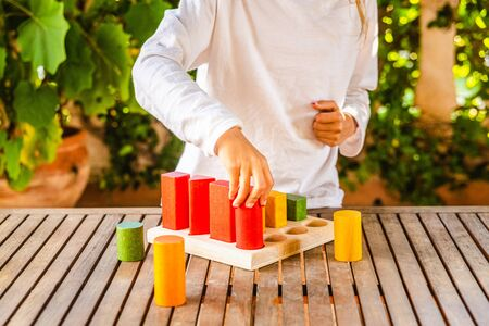 Girl using a set of wooden blocks of sequences of geometric shapes to help motor development.