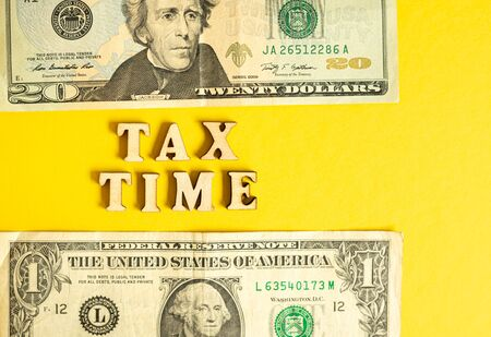 Economic phrase Tax Time isolated on yellow paper background with dollar bills. Banque d'images - 128717652