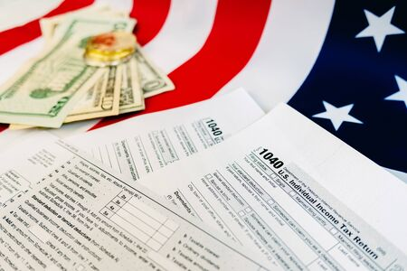 Dollar bills on a table in which the 1040 American tax payment form is filled out. Stock Photo