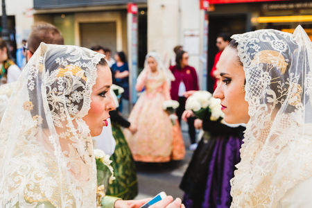 Valencia, Spain - March 17, 2019: Portrait of women dressed as falleras with the colorful and luxurious dress of Fallas.