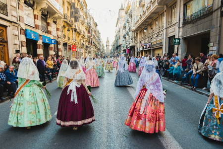 Valencia, Spain - March 17, 2019: Fallera Commission parading down Calle de la Paz, seen from behind, during the Fallas offering. 報道画像