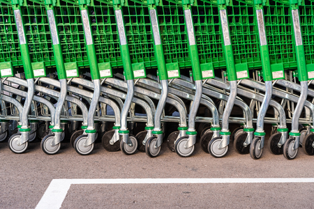 Valencia, Spain - July 3, 2019: Detail of the plastic wheels of shopping carts in a supermarket lined up.