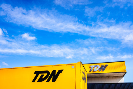 Valencia, Spain - July 30, 2019: Facade with logo of logistics companies and transport of goods by road with trucks such as TDN.