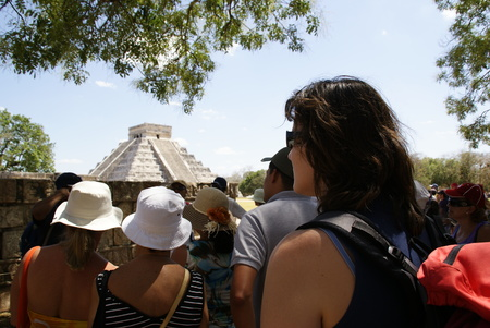 Yucatan, Mexico - March 19, 2010: Group of tourists take refuge from the sun while contemplating the temple of the sun in Chichen Itza.