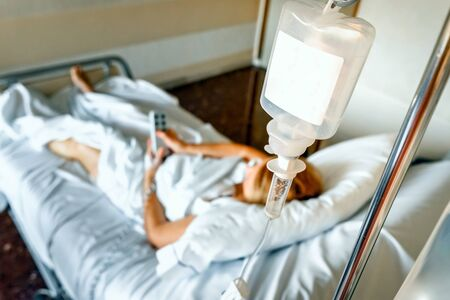 Saline solution drip  bag hanging on the bed of a sick woman. Zdjęcie Seryjne
