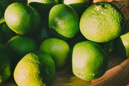 Detail of a bowl full of unripe green mandarins. Imagens