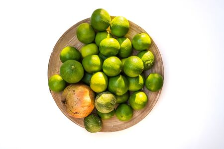 Bowl full of unripe green mandarins isolated on white background viewed from above.