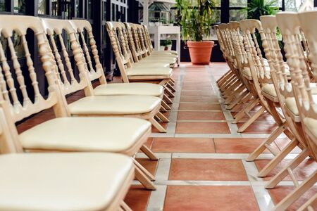 Many empty white wooden chairs lined up for a retro style event.