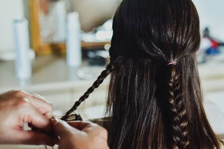 A hairdresser makes braids in the hair of a brunette woman. Zdjęcie Seryjne