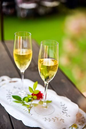 Two glasses of bubbly champagne with unfocused background of a celebration.