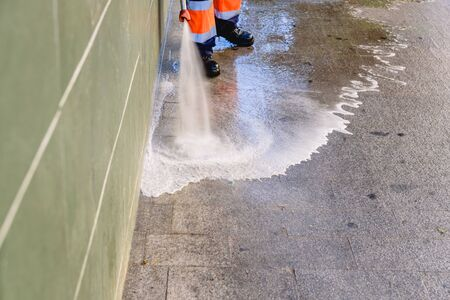 Cleaning worker throwing pressure water to clean the sidewalks of a city. Standard-Bild