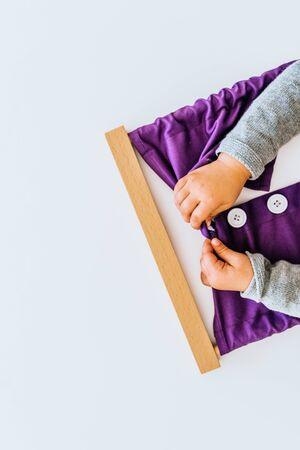 Meisje knoopt een montessori-frame dicht om de behendigheid van haar vingers te ontwikkelen.