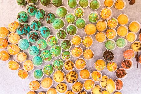 Tray with small muffins with colored topping.