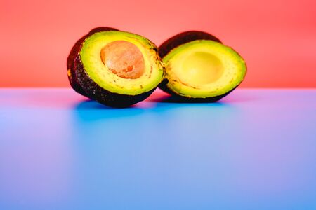 Avocados facing the camera isolated on a flat color background with copy space.