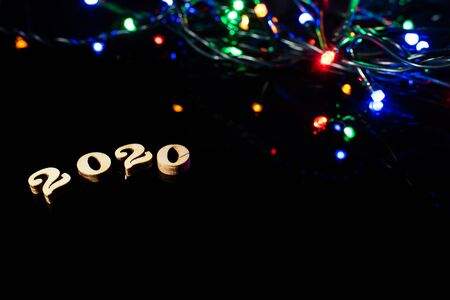 New year 2020 with numbers and bright lights on dark background and free space for text.