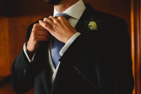 Hands of groom knotting his tie to the bridal fashion before going to the ceremony.